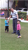 Rajendra Darda playing in garden with grandson Aryaveer and granddaughter Shanaya.